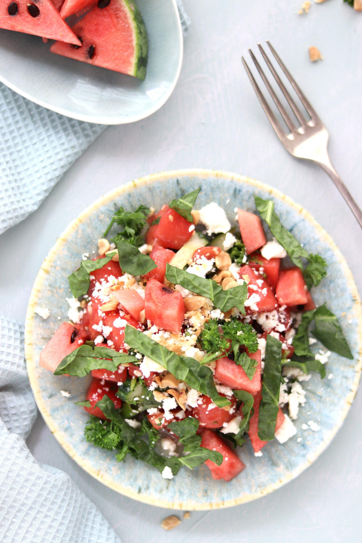 Salat aus Wassermelone, Gurken, Rucola und Feta uaf einem blauen Teller, im Hintergrund stehen Wassermelonenstückchen.