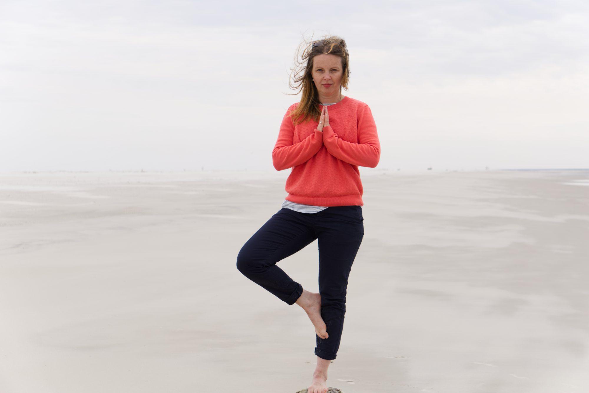 Frau steht auf einem Pfosten am Strand