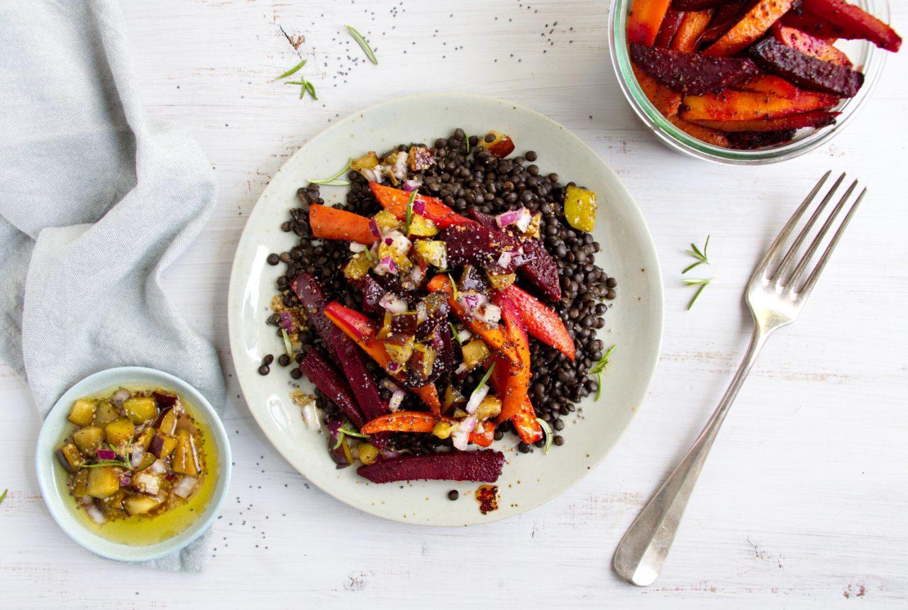 Linsen auf einem Teller mit buntem Gemüse und Dressing