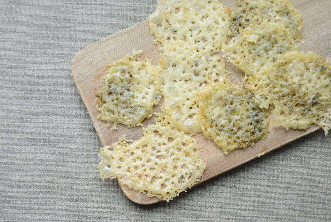 Mehrere Chips aus Käse liegen auf einem Brett